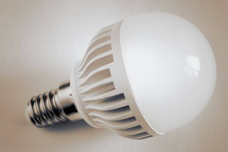On a light background, a small energy-saving lamp. The concept of energy saving. The view from the top, negative space.