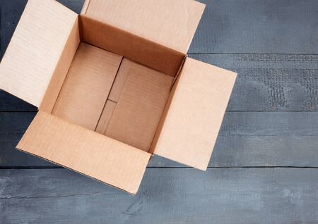 Empty open cardboard box for postal items on a wooden background. Top view, copy space 写真素材