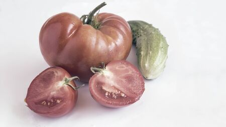 On a white background, a red ripe large tomato, sliced tomato slices and cucumber 写真素材