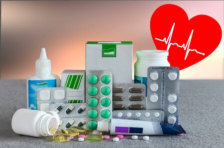 Different forms of drugs: tablets, ampoules, tinctures, blister pack on a light background with the emblem of the heart.. The place to insert the text. Medicine and pharmacy.