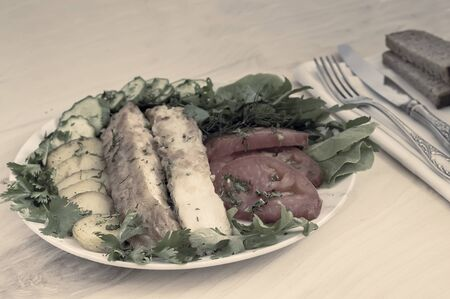 On the table on a plate two slices of fried fish, fried potatoes, cucumbers , tomatoes, salad, parsley and dill. 写真素材