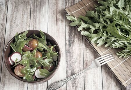 On the table in a ceramic dish, a salad of radish, tomatoes, arugula, next to a bunch of greens. The view from the top. Copy space. 写真素材