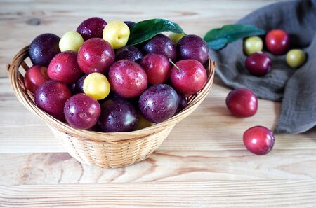On the wooden table is a wicker basket filled with ripe large plums. Foto de archivo - 134654679