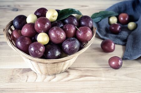 On the wooden table is a wicker basket filled with ripe large plums. Foto de archivo - 134654688