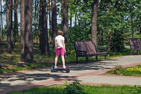 A girl on a self balancing scooter rides along the Park alley among the trees Foto de archivo - 134654755