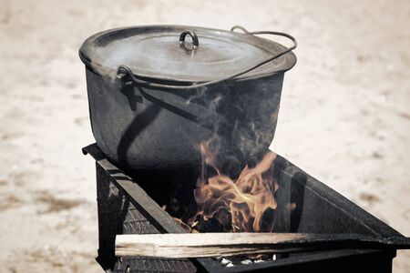 In the open air on the fire in a pot of cooked food. Foto de archivo - 134654859