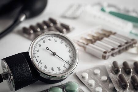 On the table is an apparatus for blood pressure measurement, which shows higher pressures. It's a hypertensive crisis. Near are medications to assist. Foto de archivo - 134654861