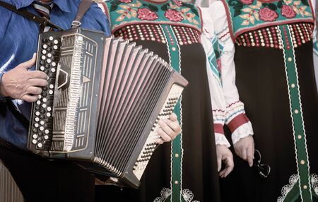 A man in national clothes plays an ancient folk musical instrument accordion in the ensemble Foto de archivo - 134654865