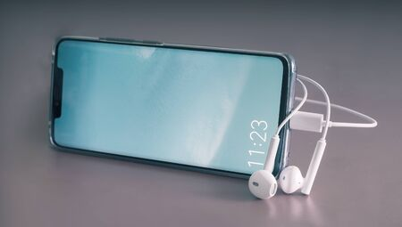 Modern smartphone and headphones on a gray background. Close-up, front view, copy space Foto de archivo - 134655284