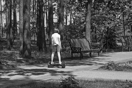 A girl on a self balancing scooter rides along the Park alley among the trees Foto de archivo - 134655297