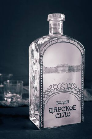 On a dark background, a beautiful large bottle of vodka Tsarskoye Selo and two glasses. Stock Photo
