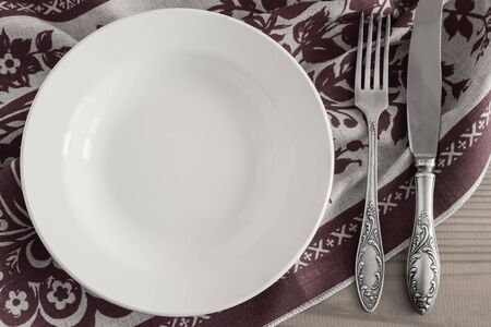 On a wooden table, a white empty plate, a knife and fork on a linen napkin with a beautiful pattern. Top view, copy space .