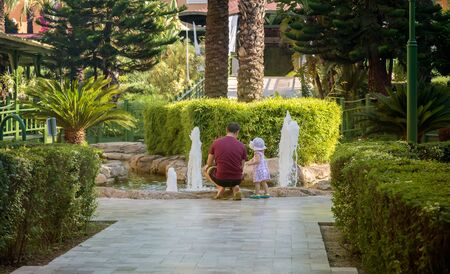 Near a small fountain in a green alley, a man and a little girl look at the water jets.