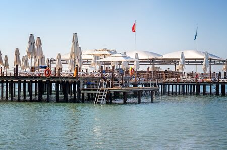 Berth with sun loungers and parasols for vacationers on the shores of the calm and clean Mediterranean sea.