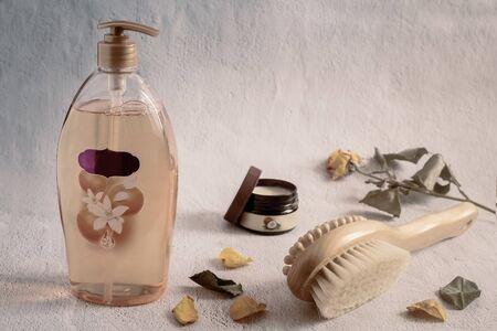 Shower gel in a large bottle, body massage brush and coconut oil for skin care. Banco de Imagens