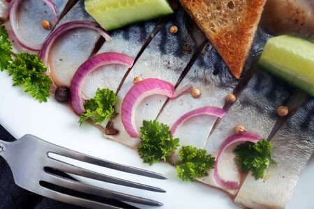 On a wooden table on a napkin plate with slices of salted mackerel, onions, parsley and a piece of bread. Top view.