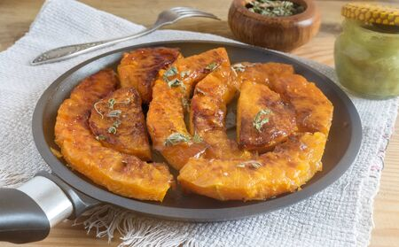 On a wooden table on a napkin pan with slices of pumpkin, baked with honey and herbs.