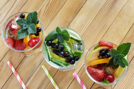 Summer refreshing cocktail of natural fruits and various berries with ice and mint leaves infused with water. Contains lemon, orange, strawberry, cherry, currant.