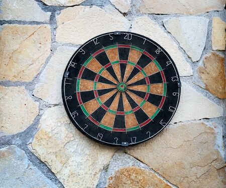 On the wall of natural stone hangs a target with numbers and sectors for playing Darts.