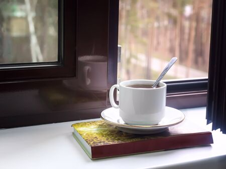 On the windowsill at the open window, a Cup of tea and a book, outside the window a view of the autumn Park. Banco de Imagens