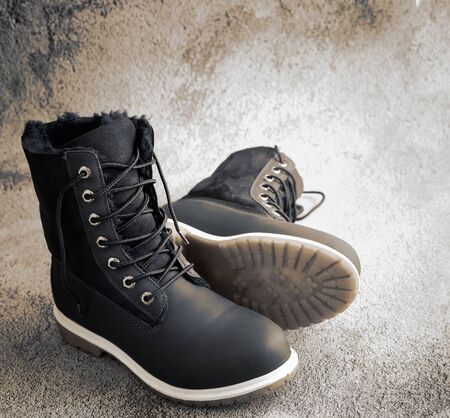 Comfortable and warm winter womens boots with faux fur inside and lacing. Presented on a light background. Side view, copy space