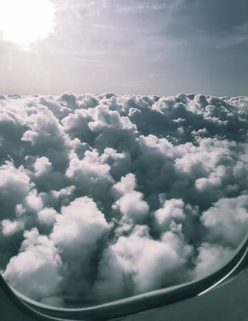 View from the window of the aircraft: clouds under the wing of the aircraft, above the clear sky and the sun