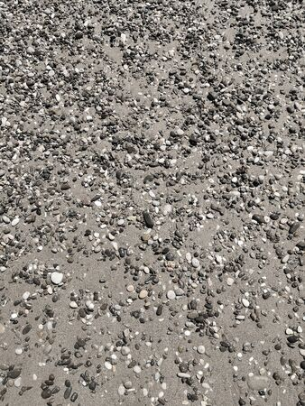 Background image: small colored sea stones on the sand on the sea beach.