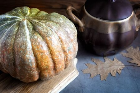 Still life: a large ripe pumpkin and a ceramic pot for cooking it. Presented in close-up