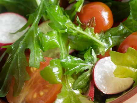 On the table in a ceramic plate salad of radishes, tomatoes, arugula. Presented close-up. The view from the top.