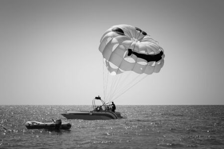 Extreme entertainment parasailing: parachuting over the sea after a boat using a cable