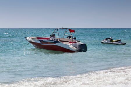 In the water near the shore-a small boat and a water scooter for sea trips.