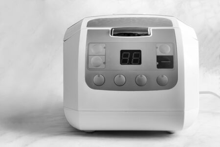 Home appliances: modern electric multi-cooker on a light background. Front view, copy space. Black and white image.