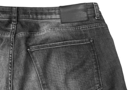 A fragment of black denim trousers with a back pocket isolated on a white background.