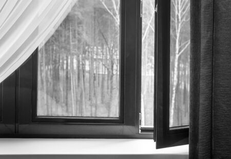 Partially open window with curtains and a view of the trees in the autumn Park