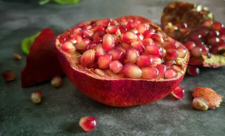 On the kitchen table, a large ripe pomegranate fruit with seeds is cut open. Presented in close-up on a dark background.