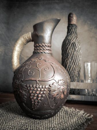 Ceramic wine jug made of red clay with a braided handle, handmade. There is a wine bottle and a glass next to it. Imagens