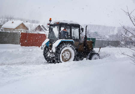 A small tractor clears the road from snow