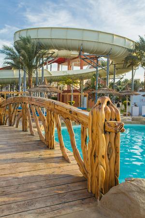 wooden bridge: Wooden bridge over swimming pool to the waterslide Stock Photo