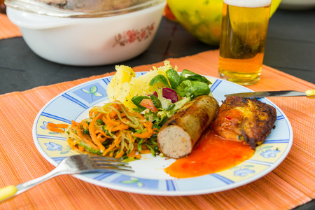 souse: Sausage, salads and potato lying on the plate to eat.