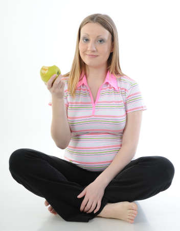 beautiful blonde woman: Portrait of a beautiful pregnant woman holding apple isolated on a white background Stock Photo