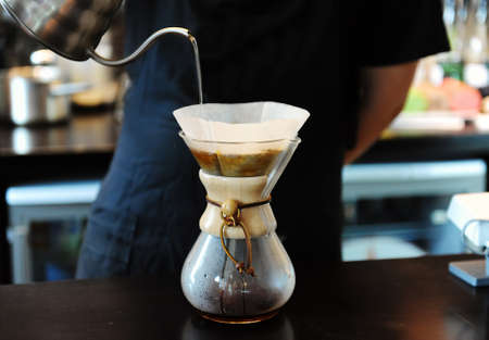 Professional barista brewing coffee in coffee shop