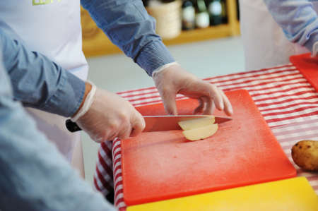 Man hands chopping fresh potato on chopping board