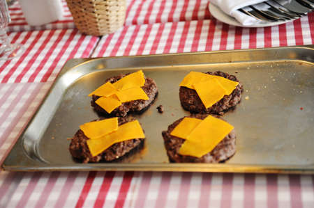 Beef or pork meat barbecue burgers for hamburger with cheddar cheese on metal pan Stock Photo