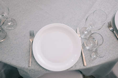 Empty white dinner plate on a table in a restaurant Stock fotó