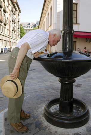 sweltering: Senior drinking from the fountain
