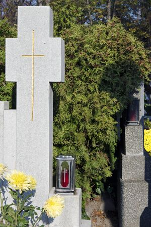 all saints  day: Cross on headstone in a cemetery on All Saints Day.
