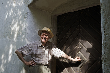enters: Senior Enters the door of the old country house Stock Photo
