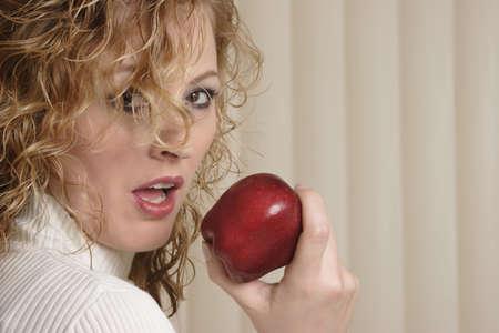 Modern Eve biting on red apple Stock Photo - 204848