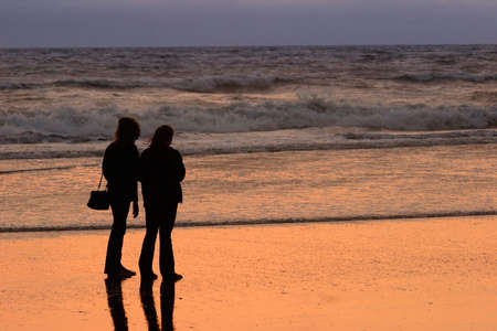 2 women watching the beach sunset stock photo picture and royalty