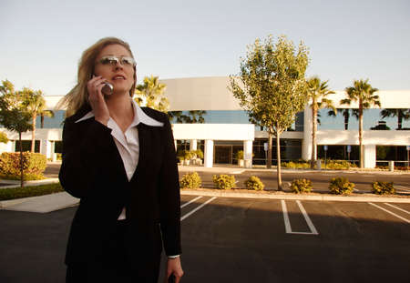 Blond Executive looking up talking on cell phone photo
